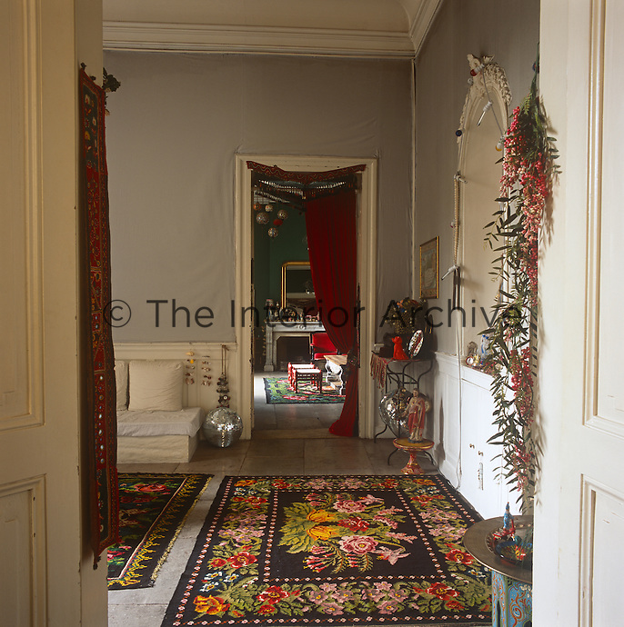 A view into a living room with grey covered walls and floral pattern rugs over a stone floor.