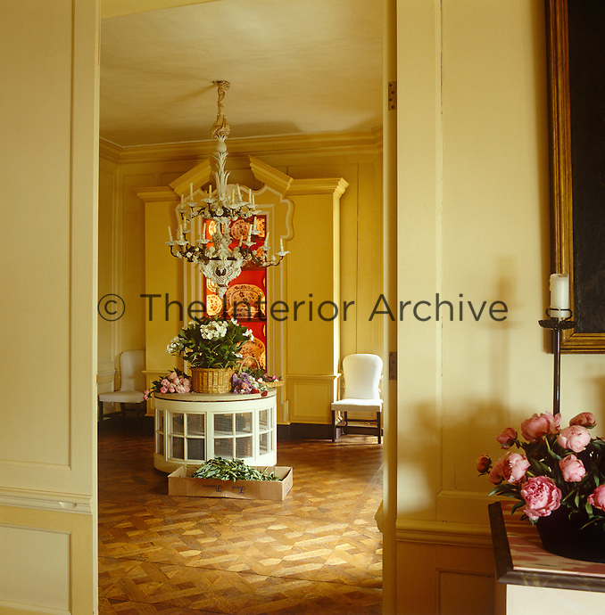 The pale parquet floor and elaborate ceramic chandelier of the ante-room is glimpsed through the door of the living room