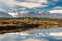 Kayaking in coastal lagoon near Okarito with views of Southern Alps, Westland Tai Poutini National Park, West Coast, UNESCO World Heritage Area, New Zealand