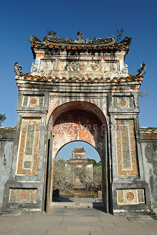 Asia, Vietnam, Hue. Gate from mausoleum to pavillion at the royal tomb of Tu Duc. Designated a UNESCO World Heritage Site in 1993, Hue is honoured for its complex of historic monuments. Many of them are scattered across the scenic countryside to the south of Hue. Often considered to be the most elegant tomb in Vietnam, the mausoleum of Tu Duc (1848-1883) was designed by the king himself. Set on a pine-forested hill, it is flanked by lotus ponds and frangipani trees.