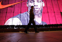 Pedestrians walk past a large Nike ad featuring NBA star Lebron James in Shanghai, China..