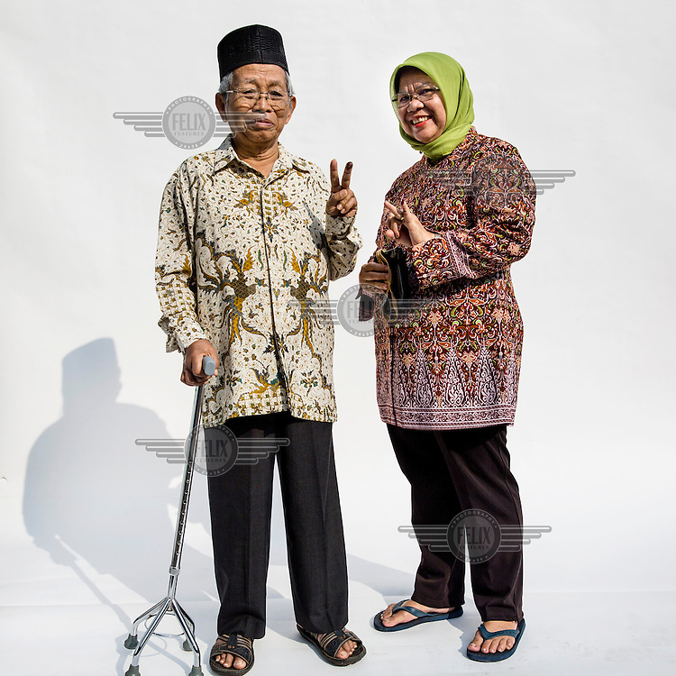 An elderly couple flash a two fingered sign, symbolising Indonesian presidential candidate Jokowi's candidacy number after they cast their votes at a polling station in Jakarta.
