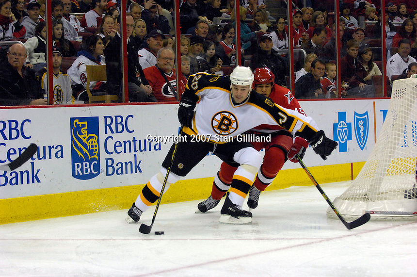 Carolina Hurricanes' David Tanabe, right, chases the Boston Bruins' Wayne Primeau (20) around the back of the net Saturday, Feb. 3, 2007 at the RBC Center in Raleigh. Boston won 4-3 in overtime.