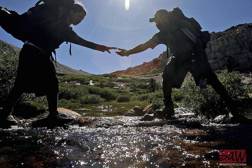 "Leslie Vega,16,left, is helped across a stream by Outward Bound Adventures guide Andrew TKTKTK, during hike in Sierras Golden Trout Wilderness. Profile of Outward Bound Adventures, a nonprofit organization that introduces at-risk urban teens to the therapeutic benefits of time spent in the wilds, there motto is; ""Share the Earth, Challenge a Child"". Known as OBA, the group brought 12 teens, all continuation high school students from the Pico Union and Watts areas of downtown Los Angeles on a 28-mile trek last month  (EDS NOTE: July 31 - August 9), OBA annually brings Los Angeles teens into the High Sierra's. After three days at a base camp and in-depth instruction, youth are led into the backcountry for six days where they are challenged to work as a team on such tasks as cooking, cleaning, camp set-up and breakdown."