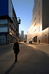Young women standing alone in Manhattan intersection early Morning, NYC, New York, USA, 2006.