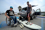 ENCINITAS, CA - MARCH 7: Paraplegic surfer and athlete Jeremy McGhee prepares to surf at Cardiff Reef on July 3, 2013 in Encinitas, California. McGhee lost use of all his muscles and feeling below his sternum after a motorcycle crash several years ago, but continues to live an adventurous lifestyle of surfing, skiing, swimming and paddling while also giving motivational public speeches. A local shaper Jeff Grygera made him a special board in which Jeremy's legs and lower bag are strapped in and supported, while he to paddles into waves with a kayak paddle and disengages from board and swim with his arms if he flips.