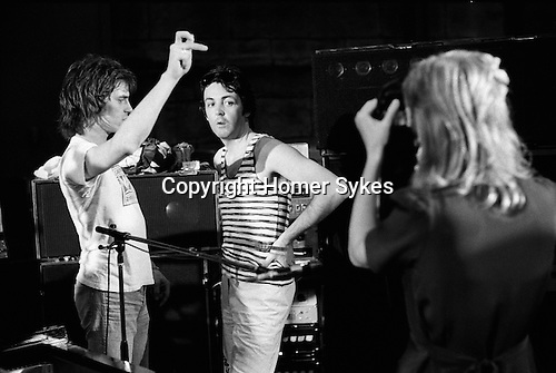 "Paul and Linda McCartney Wings Tour 1975. Linda takes a photograph of Paul at the rehearsal studio Elstree. Roadie Trevor Jones talks with Paul. The photographs from this set were taken in 1975. I was on tour with them for a children's ""Fact Book"". This book was called, The Facts about a Pop Group Featuring Wings. Introduced by Paul McCartney, published by G.Whizzard. They had recently recorded albums, Wildlife, Red Rose Speedway, Band on the Run and Venus and Mars. I believe it was the English leg of Wings Over the World tour. But as I recall they were promoting,  Band on the Run and Venus and Mars in particular."