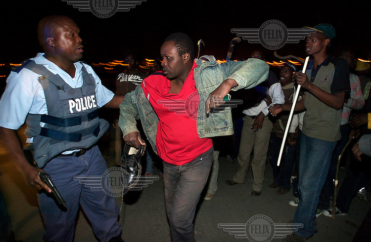 A policeman rescues a man from an angry mob who is accused of being a foreigner, in Alexandra township. The man carries a South African ID document in his left hand. Thousands of migrants have been forced to flee due to brutal xenophobic attacks on foreign African migrants living in South Africa's impoverished townships.