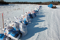 Food drop bags line the Kuskokwim River at Nikolai. Photo by Jon Little.