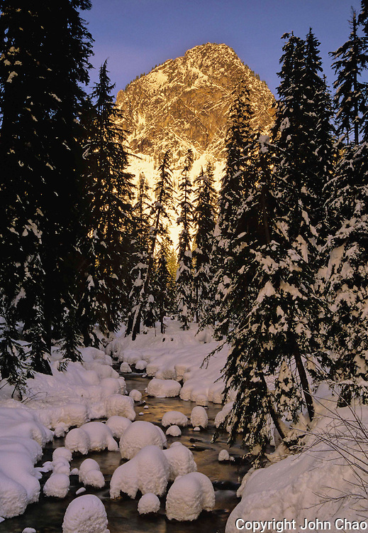 Sunset highlights Guye Peak behind a snowy winter creek at Snoqualmie Pass, Washington State