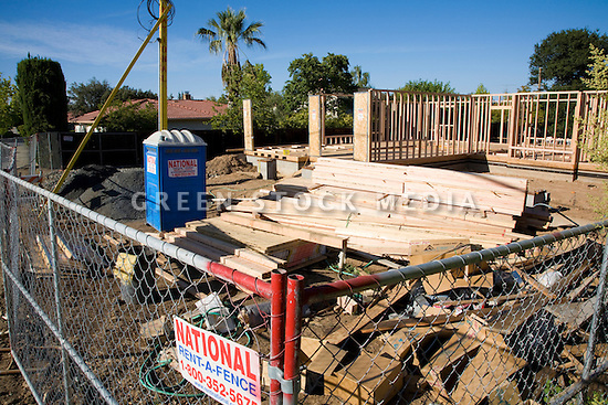 A building site of a single family house with a wooden frame in the background. The conventional building methods consume a large amount of natural resources such as trees used for lumber. Cupertino, California USA