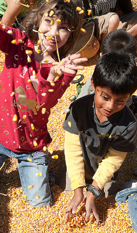Photo by Phil Grout..Ariel Hammerash (left) of Ellicott City and Alex Ornland of Columbia have fun mixing.it up in a big heap of shelled corn at the Central Maryland Research and Education.Center open house Saturday..
