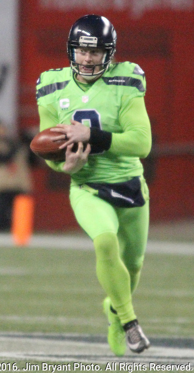 Seattle Seahawks punter Jon Ryan (9) bobbles the ball while running for 26 yards on a fake punt against the Los Angles Rams at CenturyLink Field in Seattle, Washington on December 15, 2016.  Ryan was shaken up and taken helped from the field. The Seahawks beat the Rams 24-3.   ©2016. Jim Bryant Photo. All Rights Reserved