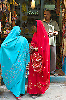 Indian women looking in shop window of jewellery shop in the city of Varanasi, Benares, Northern India