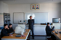 A teacher stands before a class (under the portraits of Kim Il-Sung and Kim Jong-Il) while students busy themselves with physics experiments at a model secondary school in Pyongyang, North Korea (DPRK) on 29 February 2008.