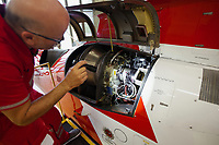 "Switzerland. Canton Ticino. Locarno Airport LSZL. The Rega base's official name is Locarno LSMO AFB (Rega 6). The paramedic Paolo Menghetti during a daily check of the engine of a  Rega Agusta AW109 SP Grand ""Da Vinci"" helicopter. All Rega helicopters carry a crew of three: a pilot, an emergency physician, and a paramedic who is also trained to assist the pilot for radio communication, navigation, terrain/object avoidance, and winch operations. The name Rega was created by combining letters from the name ""Swiss Air Rescue Guard"" as it was written in German (Schweizerische Rettungsflugwacht), French (Garde Aérienne Suisse de Sauvetage), and Italian (Guardia Aerea Svizzera di Soccorso). Rega is a private, non-profit air rescue service that provides emergency medical assistance in Switzerland. Rega mainly assists with mountain rescues, though it will also operate in other terrains when needed, most notably during life-threatening emergencies. As a non-profit foundation, Rega does not receive financial assistance from any government. The AgustaWestland AW109 is a lightweight, twin-engine, helicopter built by the Italian manufacturer Leonardo S.p.A. (formerly AgustaWestland, Leonardo-Finmeccanica and Finmeccanica). Leonardo S.p.A is an Italian global high-tech company and one of the key players in aerospace. In close collaboration with the manufacturer, the Da Vinci has been specially designed to cater for Rega's particular requirements as regards carrying out operations in the mountains. It optimally fulfills the high demands made of it in terms of flying characteristics, emergency medical equipment and maintenance. Safety, performance and space have been increased, and maintenance and noise emissions reduced. 9.09.2017 © 2017 Didier Ruef"