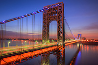 Morning rush hour traffic creates streaks of light on the George Washington Bridge as commuters cross the Hudson River between Fort Lee, New Jersey and Fort Washington, New York before sunrise on April 8, 2013.  The bridge was illuminated with blue lights in support of Autism Awareness Month.