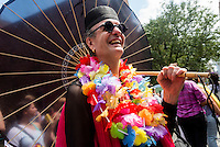New York, NY- Gay Pride Parade in the West VIllage - Man with a rainbow colored umbrella and lei enjoying the Lesbian and Gay Pride Parade on Greenwich Street in the West Village.