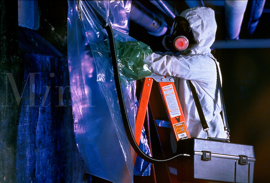 A worker dressed in protective gear removes asbestos from a building.