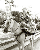 MEXICO, Maya Riviera, Mexican Cowgirl wearing sombrero sitting on horse (B&W)