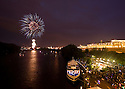 Fireworks explode over the Connecticut River during Hartford's riverfront celebration of Independence Day. The Lady Katherine riverboat and the Connecticut Convention Center are visible.