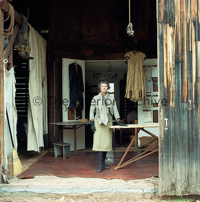 Portrait of designer and artist J Morgan Puett standing in the barn that houses her archive of beeswaxed fashion designs