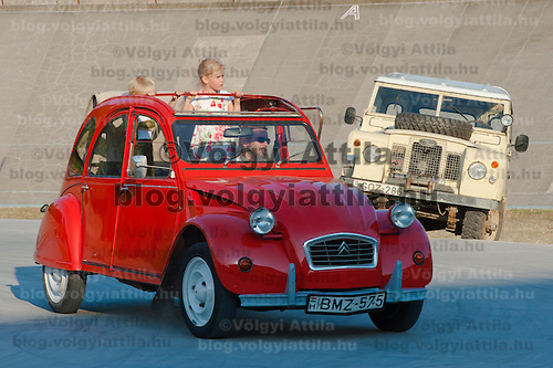 Children in an oldtimer attend a hIstoric car race in Budapest, Hungary on September 17, 2011. ATTILA VOLGYI
