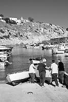 Castro Marina - Salento - Puglia - Alcuni pescatori aiutano uno di loro a spingere in acqua la barca per la pesca.