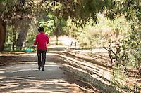 Woman Walking on Trail at Ralph B. Clark Regional Park in Buena Park