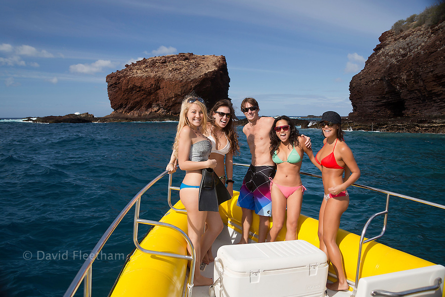 A group of young people (MR) pose on a hard bottom inflatable off Lanai.  In the background is the Lanai landmark, Puu Pehe, also known as Sweetheart Rock, rising from the waters between Hulopoe Bay and Manele Bay, Hawaii.
