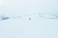 Single female hiker in whiteout conditions in winter on ascent of Matmora mountain peak, Austvågøy, Lofoten Islands, Norway