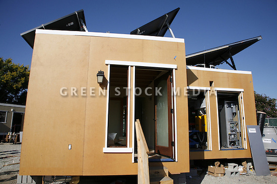 Side view of a solar house under construction with siding made from Richlite paper pulp from certified managed forests in North America. Solar panels are visible on the roof. Santa Clara University Solar Decathlon 2007 (scusolar.org).