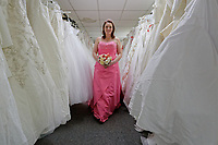 "COPY BY TOM BEDFORD<br /> Pictured: Member of staff Michelle Curry who has been trying on some of the dresses at the John Pye Auctions warehouse in Pyle, south Wales, UK.<br /> Re: A bride cried tears of joy after her missing wedding dress was found among a pile of 20,000 gowns in a warehouse.<br /> Meg Stamp, 27, paid £1,300 for the beautiful ivory lace dress but it  was seized by liquidators after a bridal company went bust.<br /> It was boxed up along with 20,000 others and due to be sold for a knock-down price at auction.<br /> But determined Meg banged on the auctioneer door saying: ""I want my dress back"".<br /> Staff at John Pye auctioneers in Port Talbot spent three hours sifting through boxes until they finally found Meg's dream dress."
