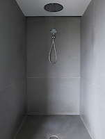 The minimal walk-in shower is lined with limestone tiles