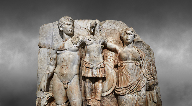 Close up of Roman Sebasteion relief sculpture of emperor Augustus and Goddess Victory, Aphrodisias Museum, Aphrodisias, Turkey.  Against a grey background.<br /> <br /> The naked emperor Augustus stands in majesty with the winged goddess Victory(Nike). He carried a spear and has an eagle, the bird representing Zeus, at his feet. Victory is crowning a military trophy - a rough post with enemy armour attached to it. Beneath the trophy is a barbarian captive, his hands tied behind his back.