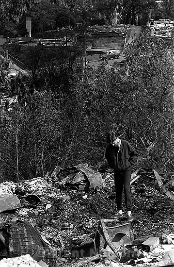 Man standing in the remains of his family's home after the Oakland Hills Fire.<br />