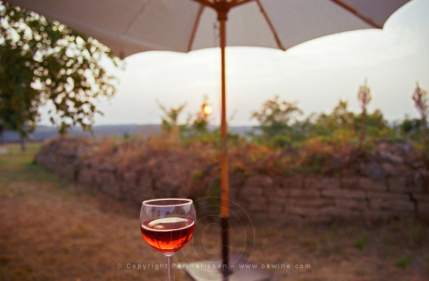 Hot summer in Burgundy, sunset, a glass of cool rose wine, a sun umbrella