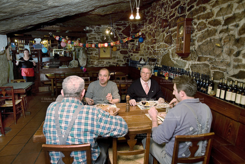 Switzerland. Canton Ticino. Ludiano. Grotto Sprüch. Lunch. Milena Rusconi, the owner, carries plates on both hands and walks toward her guests' table. Wood tables, stones walls and rock on the roof. Ludiano is located in the Blenio valley. 17.03.09 © 2009 Didier Ruef