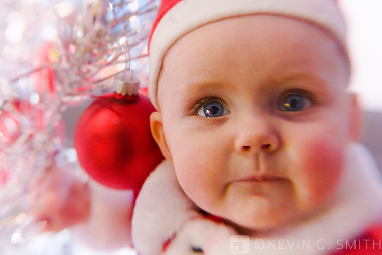 Close up of 4 month old infant, caucasian, in Santa suit in front of 60's retro aluminum christmas tree, selective focus.