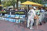 An artist with paintings for sale in Harvard Square, Cambridge, MA