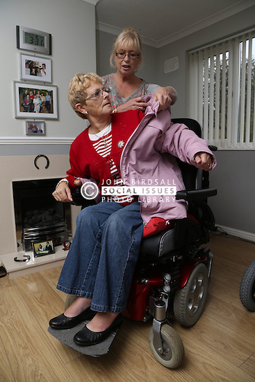 Carer putting Wheelchair user's coat