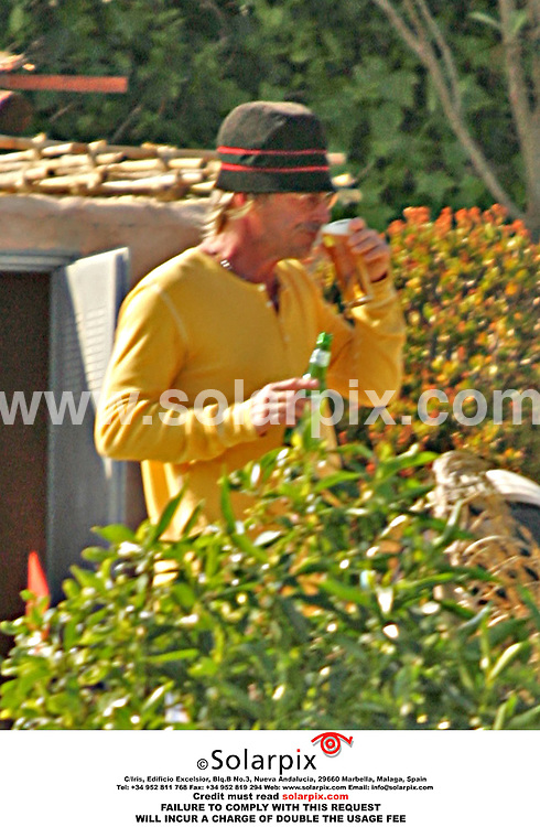 "ALL-ROUND EXCLUSIVE PICTURES FROM SOLARPIX.COM.*MUST CREDIT SOLARPIX.COM OR DOUBLE USAGE FEE*.Ex "" Jam"" and ""Style Council"" frontman, Paul Weller was spotted on the southern coast of Spain at the weekend as he holidayed with his family. The ""Mod Father"" swigged bottles of beer while relaxing by the pool before putting on his hat and setting off for a walk with his baby stroller..REF:  2240 SCR"