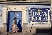 Peru. Woman in traditional dress walking past a blue door with a large Inca Kola sign.