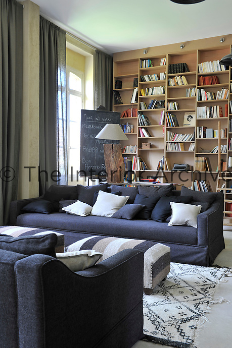 Comfortable sofas in the living area are covered in practical grey linen, whilst behind an entire wall is covered with bookshelves