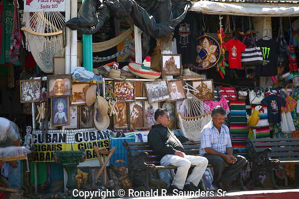 TWO MEN SIT OUTSIDE MEXICAN SOUVENIR SHOP