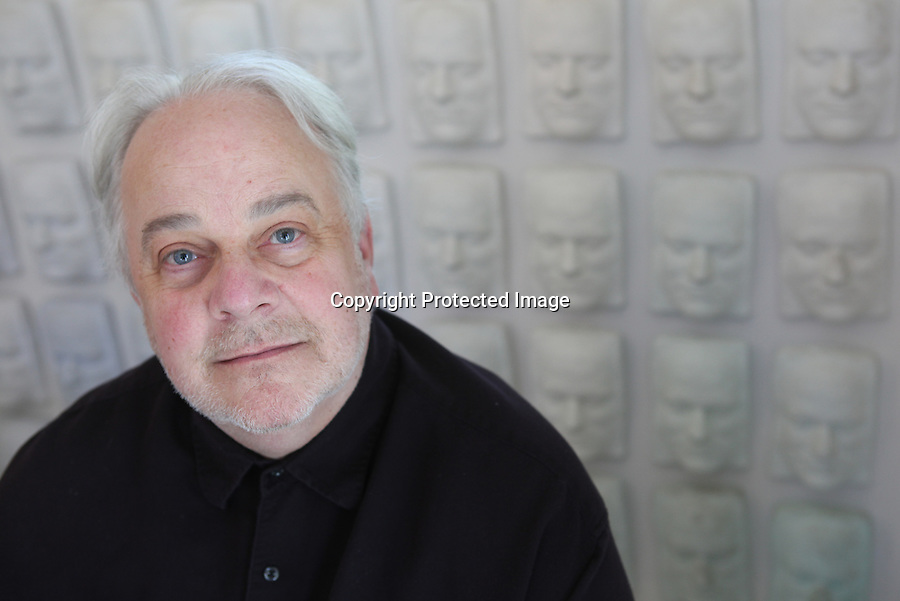 "Artist and collector, Robert Rindler is photographed in front of a wall of faces in his studio in Wellfleet, Ma.  The faces are all duplicates of Rindler's own face--a series he created many years ago.   ""Our home is our biggest collection and the images and objects we surround ourselves with are an ongoing collage installation,"" says Rindler of the home he and long-term partner, James Connors, share.   5/6/11 Julia Cumes"