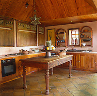 A series of antique Sumatran carved panels adorn the walls of the kitchen