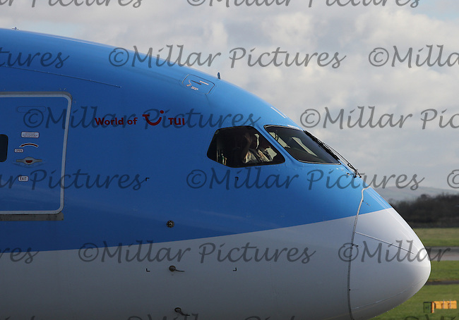 A crew member waving on a Thomson Airways Boeing 787-8 Dreamliner Registration G-TUIA taxying at Manchester Airport on 14.2.16 bound for Punta Cana International Airport .