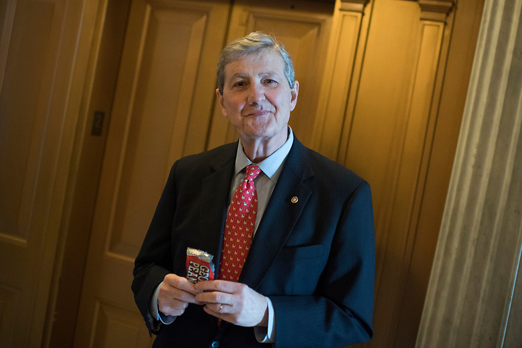 UNITED STATES - MARCH 15: Sen. John Kennedy, R-La., eats a bag of Georgia peanuts in the Capitol after a vote, March 15, 2017. (Photo By Tom Williams/CQ Roll Call)
