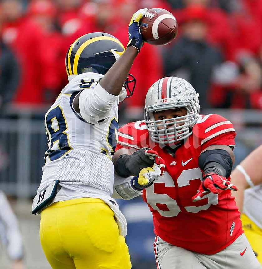 Ohio State Buckeyes defensive tackle Michael Bennett (63) gets in the backfield and tries to sack Michigan Wolverines quarterback Devin Gardner (98) in the 3rd quarter of their game at Ohio Stadium in Columbus, Ohio on November 29, 2014.  (Dispatch photo by Kyle Robertson)